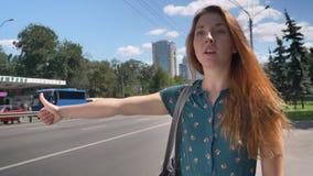 Молодая очаровательная женщина имбиря с сумкой окликает такси, городскую улицу с дорогой в предпосылке, женской вызывая кабине видеоматериал