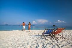 Молодая пара бежит в тропическое море Стоковые Изображения
