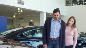 Молодая пара выбирает автомобиль на дилерских полномочиях стоковые изображения