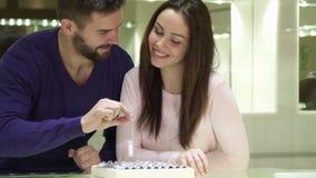 Молодая пара выбирает обручальные кольца на ювелирном магазине стоковые фотографии rf