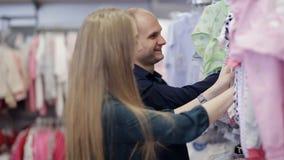 Молодая пара выбирает одежду для младенца в магазине видеоматериал