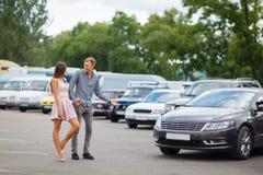 Молодая пара выбирает подержанный автомобиль в выставочном зале улицы стоковое изображение rf