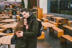 Молодая пара в любов и девушке и стойка студента обнимая около таблиц кафа террасы улицы закрыли пустое снаружи стоковое изображение rf