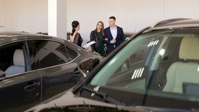 Молодая пара в любов покупает автомобиль в выставочном зале, они советует с с продавцом акции видеоматериалы