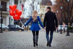 Молодая пара в пальто держит сердце воздушных шаров в cit Стоковое Изображение