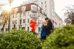 Молодая пара в пальто держит сердце воздушных шаров в cit Стоковая Фотография