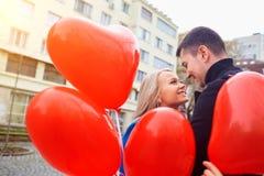 Молодая пара в пальто держит сердце воздушных шаров в cit Стоковое Изображение RF