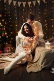 Молодая пара в светах и украшении рождества, одетых в белом, ель на темной деревянной предпосылке, концепции зимнего отдыха стоковое фото rf