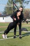 Молодая пара делая Trx связывает тренировку в парке Стоковое Фото