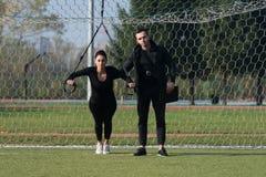 Молодая пара делая Trx связывает тренировку в парке Стоковая Фотография RF
