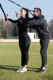 Молодая пара делая Trx связывает тренировку в парке Стоковое фото RF