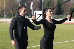 Молодая пара делая Trx связывает тренировку в парке Стоковая Фотография