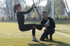 Молодая пара делая Trx связывает тренировку в парке Стоковые Фото