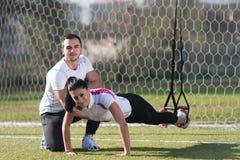 Молодая пара делая Trx связывает тренировку в парке Стоковое Изображение RF