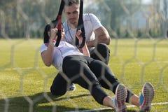 Молодая пара делая Trx связывает тренировку в парке Стоковое Изображение