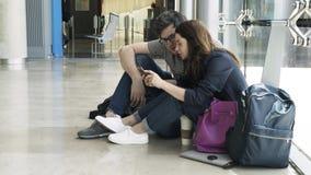 Молодая пара ждет их полет в авиапорт Валенсии, взгляд со стороны акции видеоматериалы