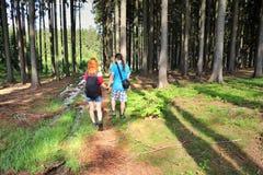 Молодая пара идя через лес стоковая фотография
