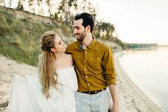 Молодая пара имеет потеху и идет на береговую линию моря Новобрачные смотря один другого с нежностью романтично Стоковое Изображение