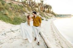 Молодая пара имеет потеху и идет на береговую линию моря Новобрачные смотря один другого с нежностью романтично Стоковое фото RF