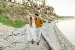 Молодая пара имеет потеху и идет на береговую линию моря Новобрачные смотря один другого с нежностью романтично Стоковые Изображения
