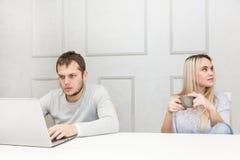Молодая пара имеет человека завтрака a работает за ноутбуком, пробуренная женщина смотрит к стороне стоковые изображения