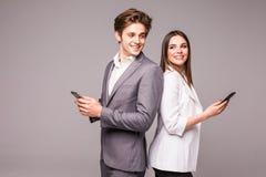 Молодая пара использует умные телефоны и усмехается пока стоящ спина к спине на серой предпосылке Посмотрите один другого стоковое изображение rf