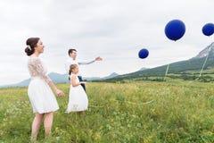 Молодая пара и их дочь в платьях свадьбы идут в природу с воздушными шарами стоковое фото rf