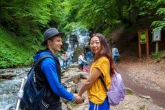Молодая пара пересекая поток горы пока вне идущ совместно Путешественники стоят около водопадов стоковая фотография rf