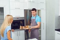 Молодая пара печет печенья в кухне стоковая фотография rf