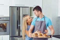 Молодая пара печет печенья в кухне стоковое изображение