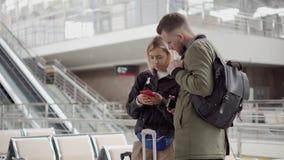 Молодая пара проверяет информацию в положении смартфона в зале аэропорта акции видеоматериалы