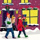 Молодая пара с покупками идет на улицу украшенную для рождества стоковое фото