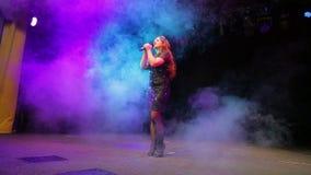 Молодая певица redhead с микрофоном в ее руках в черном платье поет на росте этапа полностью акции видеоматериалы
