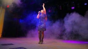 Молодая певица redhead с микрофоном в ее руках в черном платье поет на росте этапа полностью сток-видео