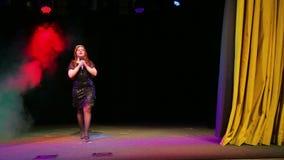Молодая певица redhead с ростом микрофона полностью входит в этап и начинает петь видеоматериал