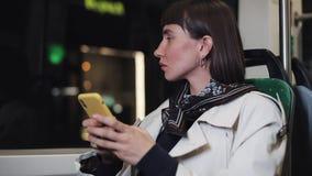 Молодая подавленная женщина сидя публично переход, смотря из окна поезда Она держа смартфон в ее руке сток-видео