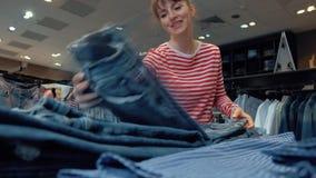 Молодая позитивная женщина-продавец денимовой одежды сглаживает вещи акции видеоматериалы