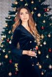 Молодая празднуя женщина в черном платье Красивый модельный бокал владением над интерьером рождества стоковые изображения rf