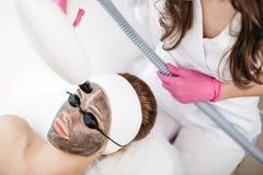 Молодая прелестная женщина с изумлёнными взглядами маски и безопасности получает обработку стороны и ультразвука лазера в професс стоковые фотографии rf