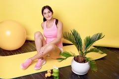 Молодая привлекательная атлетическая женщина сидя на поле на фитнесе Teppich штейновом после деятельности в спортзале стоковое фото