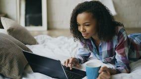 Молодая привлекательная африканская девушка используя компьтер-книжку для делить социальные средства массовой информации лежа в к акции видеоматериалы
