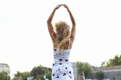 Молодая привлекательная белокурая девушка поднимая ее оружия вверх над ее головой Стоковые Фотографии RF