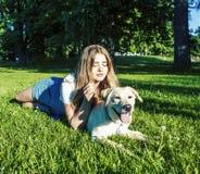 Молодая привлекательная белокурая женщина играя с ее собакой в зеленом парке на лете, концепции людей образа жизни стоковое фото rf