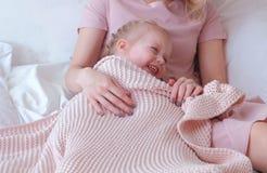 Молодая привлекательная белокурая мама играет прятк с ее маленькой очаровательной дочерью в розовых платьях Стоковая Фотография