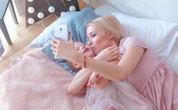 Молодая привлекательная белокурая мама показывает что-то в мобильном телефоне к ее маленькой очаровательной дочери в розовых плат Стоковая Фотография