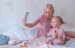 Молодая привлекательная белокурая мама показывает что-то в мобильном телефоне к ее маленькой очаровательной дочери в розовых плат Стоковые Изображения