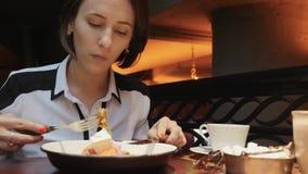 Молодая привлекательная бизнес-леди имеет обед в уютном ресторане Еда вегетарианского салата и выпивать кофе r акции видеоматериалы