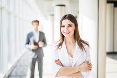 Молодая привлекательная бизнес-леди с пересеченными руками перед бизнесменом команда мегафона человека повелительницы кофе дела Стоковая Фотография RF