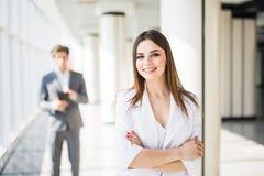 Молодая привлекательная бизнес-леди с пересеченными руками перед бизнесменом команда мегафона человека повелительницы кофе дела Стоковое фото RF