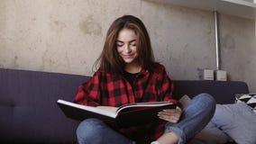 Молодая привлекательная девушка брюнет говоря что-то и усмехаясь пока читающ книгу акции видеоматериалы